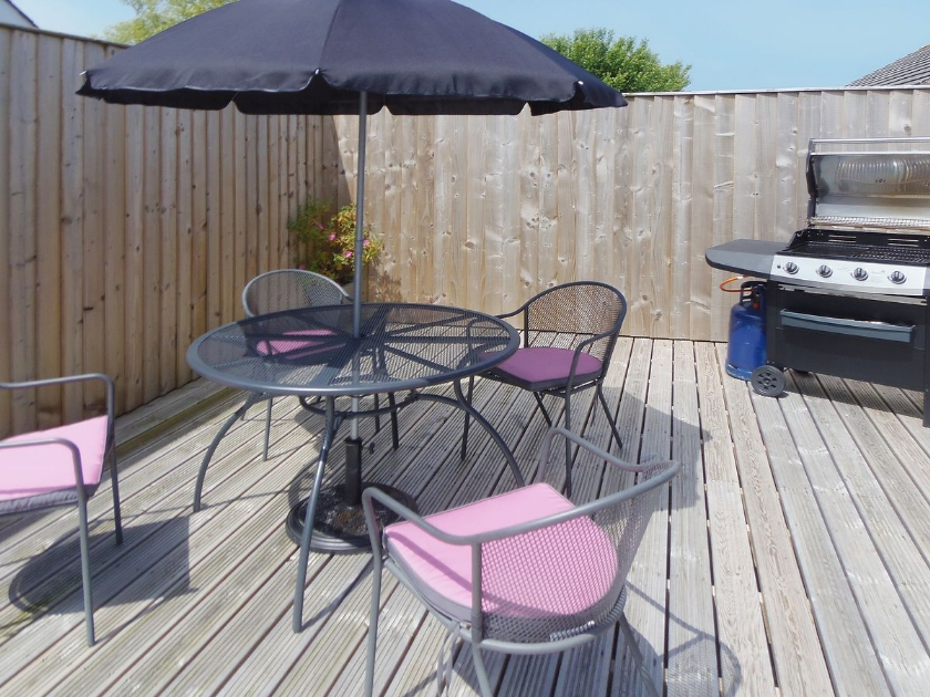 garden with decking and lawned area with garden furniture and BBQ