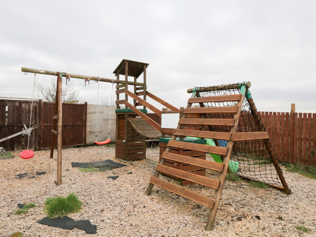 Lawned garden, shared patio with furniture, and children's play area