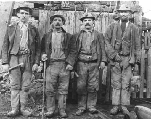 Miners with their candle lights in their hats